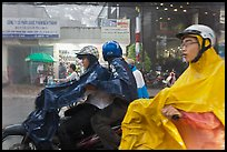 Motorcycle riders during afternoon mooson. Ho Chi Minh City, Vietnam (color)