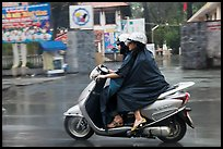 Women ride motorcycle in the rain. Ho Chi Minh City, Vietnam