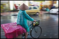 Woman rides bicycle in the rain. Ho Chi Minh City, Vietnam