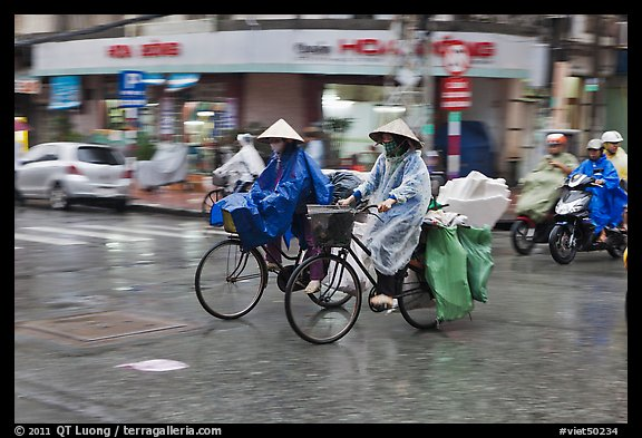 Women riding bicyles in the rain. Ho Chi Minh City, Vietnam (color)