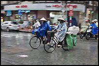 Women riding bicyles in the rain. Ho Chi Minh City, Vietnam