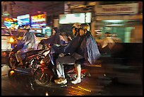 Motorcyle riders at night, dressed for the rain. Ho Chi Minh City, Vietnam
