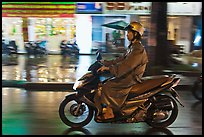 Riding motorcyle on rainy night. Ho Chi Minh City, Vietnam