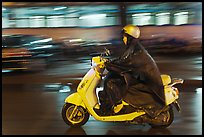 Scooter rider on rainy night. Ho Chi Minh City, Vietnam