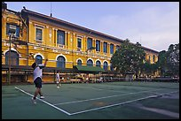 Men play tennis in front of colonial-area courthouse. Ho Chi Minh City, Vietnam