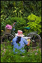Woman reading newspaper next to bicycle in park. Ho Chi Minh City, Vietnam ( color)