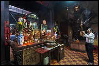 Man in prayer, with fierce statue of general behind, Jade Emperor Pagoda, district 3. Ho Chi Minh City, Vietnam (color)