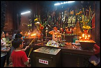 Man lightening candles, Jade Emperor Pagoda, district 3. Ho Chi Minh City, Vietnam (color)