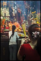 Women holding incense sticks, Phuoc Hai Tu pagoda, District 3. Ho Chi Minh City, Vietnam (color)