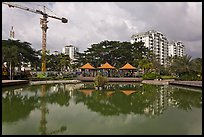Reflecting pool, completed residential buildings, and crane, Phu My Hung, district 7. Ho Chi Minh City, Vietnam (color)