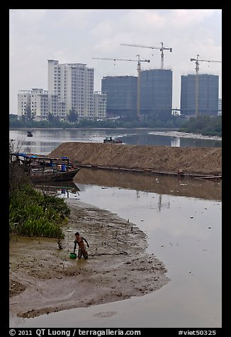 Man wading in mud, with background of towers in construction, Phu My Hung, district 7. Ho Chi Minh City, Vietnam (color)