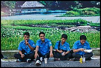 Uniformed students eating in front of backdrop depicting rural landscape. Ho Chi Minh City, Vietnam (color)