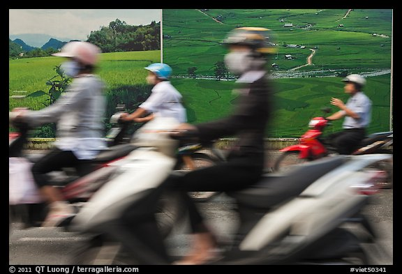 Motorbike riders speeding in front of backdrops depicting traditional landscapes. Ho Chi Minh City, Vietnam (color)