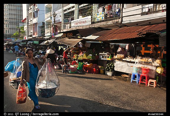 Woman carrying goods on street market. Ho Chi Minh City, Vietnam