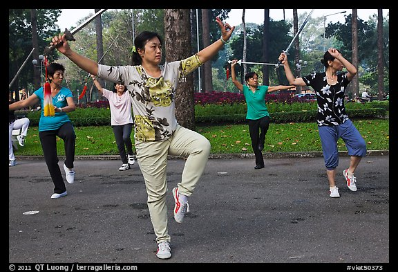 People practicisng Tai Chi with swords, Tao Dan Park. Ho Chi Minh City, Vietnam (color)