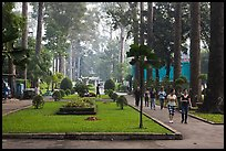 People strolling in alley below tall trees, Cong Vien Van Hoa Park. Ho Chi Minh City, Vietnam (color)
