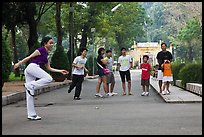 Young woman playing footbag as audience watches, Cong Vien Van Hoa Park. Ho Chi Minh City, Vietnam (color)