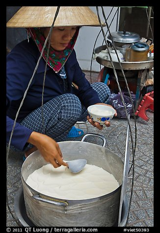 Woman serving a bowl of soft tofu. Ho Chi Minh City, Vietnam (color)