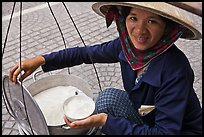 Woman smiling while handling bowl of soft tofu. Ho Chi Minh City, Vietnam (color)