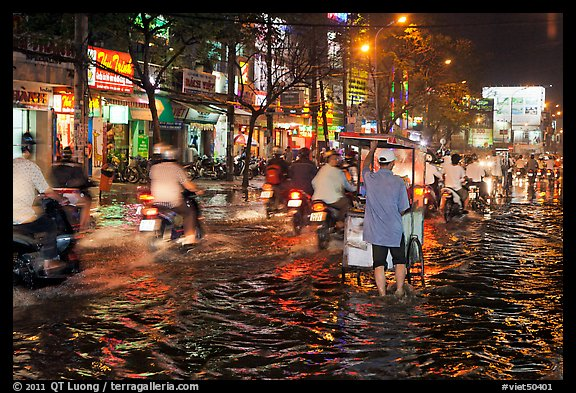 Traffic passes man pushing food cart on flooded street at night. Ho Chi Minh City, Vietnam (color)