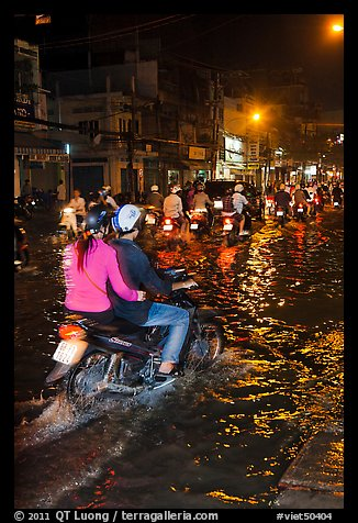 Couple riding motorcycle on flooded street at night. Ho Chi Minh City, Vietnam (color)