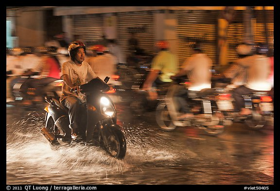 Man riding motorbike on flooded street seen against riders going in opposite direction. Ho Chi Minh City, Vietnam (color)