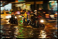 Women riding motorcyles at night in water. Ho Chi Minh City, Vietnam ( color)