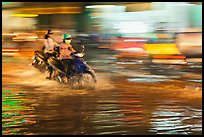 Motorcycle riders, water splashes, and streaks of light. Ho Chi Minh City, Vietnam ( color)