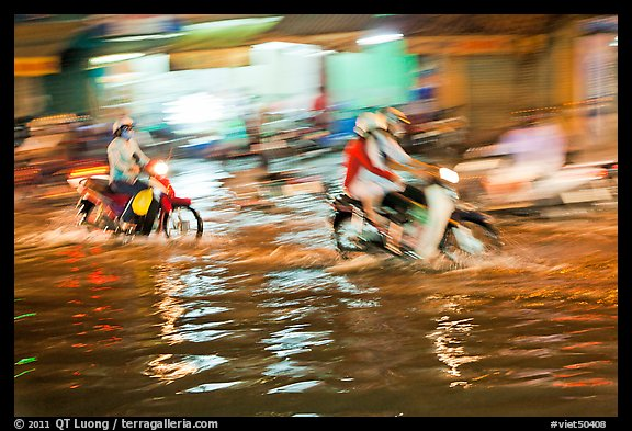 Motion-blured exposure of riders on flooded street at night. Ho Chi Minh City, Vietnam (color)