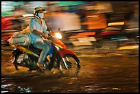 Motorcycle rider photographed with panning motion at night. Ho Chi Minh City, Vietnam ( color)