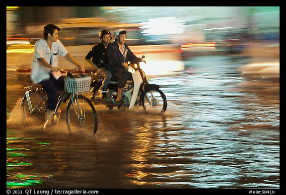 Bicyle and motorbike riders on monsoon-flooded street. Ho Chi Minh City, Vietnam (color)