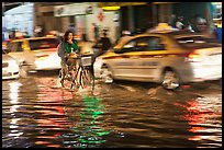Women riding a bicycle on a flooded street at night. Ho Chi Minh City, Vietnam (color)