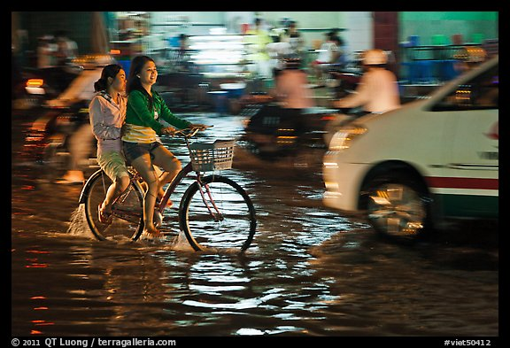 Women sharing a bicycle ride at night on a water-filled street. Ho Chi Minh City, Vietnam (color)
