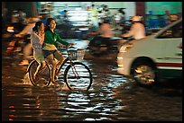 Women sharing a bicycle ride at night on a water-filled street. Ho Chi Minh City, Vietnam ( color)