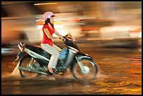 Woman riding on water-filled street, and light streaks. Ho Chi Minh City, Vietnam ( color)