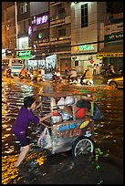 Vendor pushing foot car into the water at night. Ho Chi Minh City, Vietnam ( color)