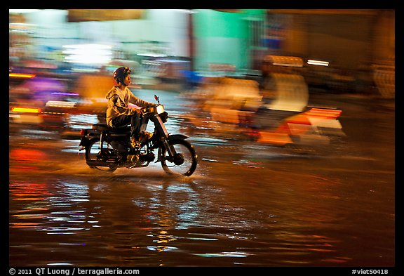 Motorcyclist speeding on wet street at night, with streaks giving sense of motion. Ho Chi Minh City, Vietnam (color)