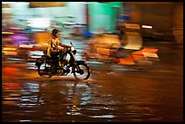 Motorcyclist speeding on wet street at night, with streaks giving sense of motion. Ho Chi Minh City, Vietnam ( color)
