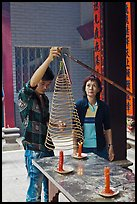 Man getting ready to hang incense coil, Thien Hau Pagoda. Cholon, District 5, Ho Chi Minh City, Vietnam (color)