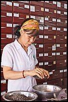 Woman weighting preparing traditional medicinal ingredients. Cholon, Ho Chi Minh City, Vietnam