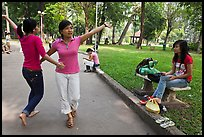 Young women dancing to sound of mobile phone, Cong Vien Van Hoa Park. Ho Chi Minh City, Vietnam (color)