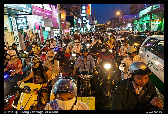 Street packed with motorcycles and vehicles at dusk. Ho Chi Minh City, Vietnam (color)
