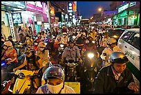 Street packed with motorcycles and vehicles at dusk. Ho Chi Minh City, Vietnam ( color)