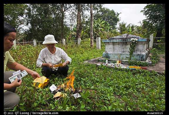 Women burning fake money as offering, Ben Tre. Mekong Delta, Vietnam