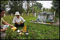Women burning fake money as offering, Ben Tre. Mekong Delta, Vietnam (color)