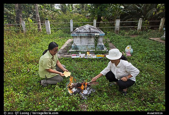 Women burning notes as offering in cemetery, Ben Tre. Mekong Delta, Vietnam (color)