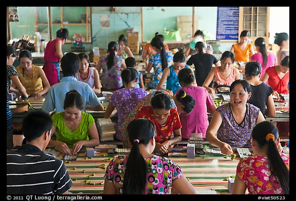 Women packing coconut candy in factory. Ben Tre, Vietnam (color)