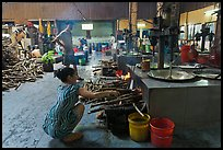 Woman feeding furnace in cococut candy factory. Ben Tre, Vietnam ( color)