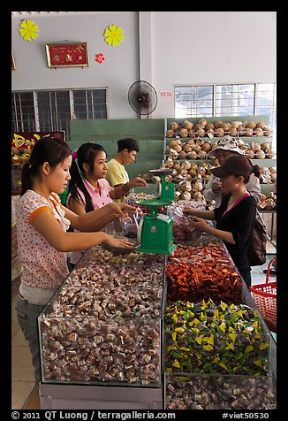 Women packing coconut candy for sale. Ben Tre, Vietnam (color)