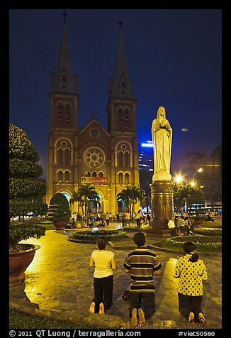 Family in prayer outside Notre-Dame Basilica at night. Ho Chi Minh City, Vietnam (color)
